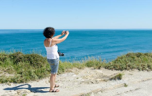 Mooie vrouw maakt een foto van de oceaan