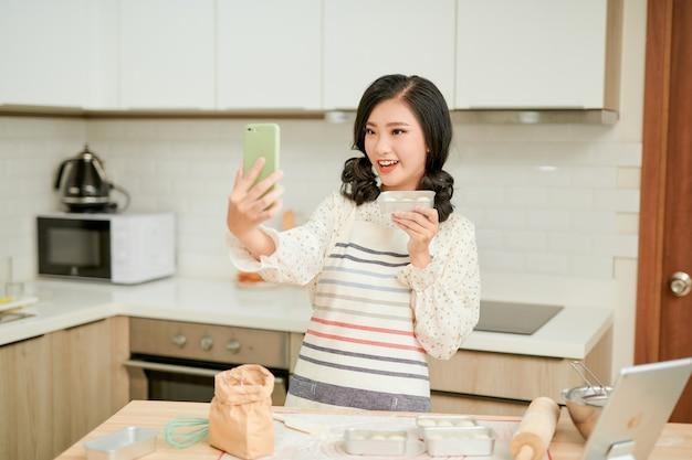 Mooie vrouw maakt foto met vers rauw cakebeslag op een bakplaat, vrouwenhanden geschilderd in bloem die de cake maakt makes