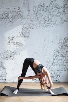 Mooie vrouw maakt hellingen naar het been thuis tegen een witte bakstenen muur