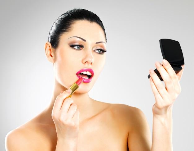 Mooie vrouw maakt make-up roze lippenstift op lippen toe te passen.