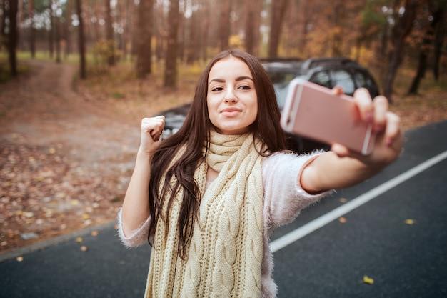 Mooie vrouw maakt selfie. meisje gebruikt een smartphone. close-up van de hand. herfst concept. herfst bos reis met de auto.