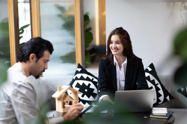 Mooie vrouw makelaar die online presentatie op laptop in kantoor aanbiedt en toont aan knappe man.
