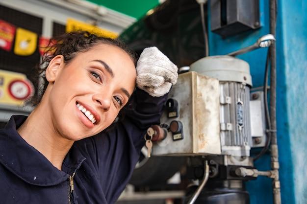 Mooie vrouw mechanica in uniform ontspannen na het werken in auto service met opgeheven voertuig en rapportage.