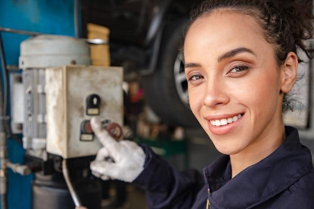 Mooie vrouw mechanica in uniform werkt in auto service met opgeheven voertuig en hydraulische bedieningsknop.