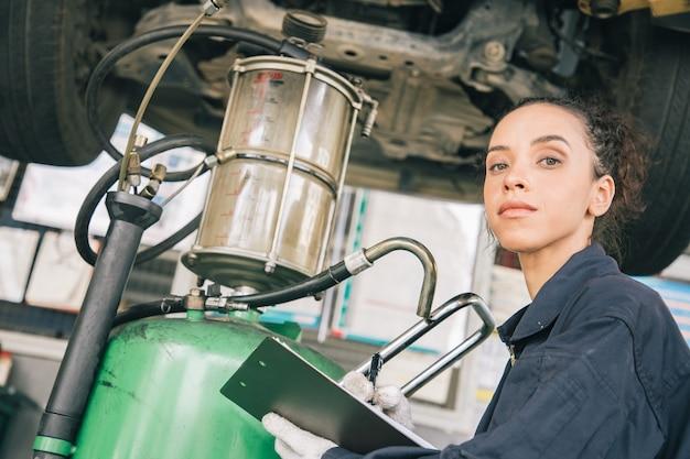 Mooie vrouw mechanica in uniform werkt in auto-service met opgeheven voertuig en papieren rapportage.