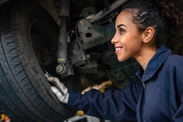 Mooie vrouw mechanica in uniform werkt in auto-service met opgeheven voertuig en rapportage.