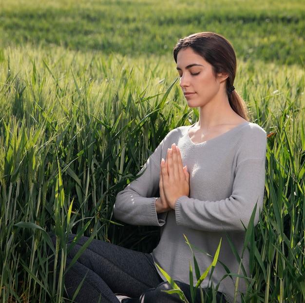 Mooie vrouw mediteren in de natuur