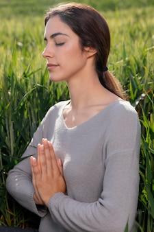 Mooie vrouw mediteren in de natuur Gratis Foto