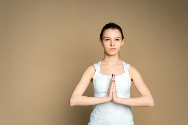 Mooie vrouw mediteren in yoga lotuspositie. ze ziet er vredig, kalm en zen uit. overweging en bidden