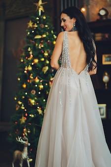 Mooie vrouw meisje in de studio van het nieuwe jaar poseren, foto nieuwjaar fotosessie. mooi meisje in een luxe jurk met slanke benen. kerstmis, winter, geluk concept.
