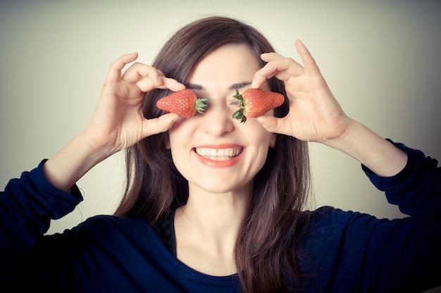 Mooie vrouw met aardbeien op ogen