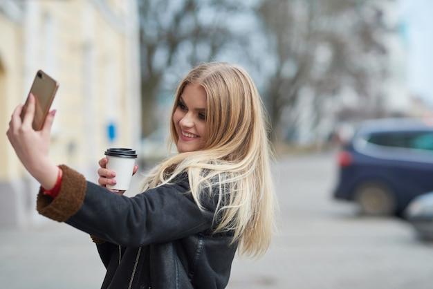 Mooie vrouw met afhaalmaaltijden koffie in papieren beker en selfie te nemen tijdens het wandelen door de straat van de stad