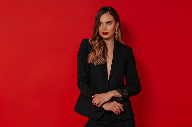 Mooie vrouw met avond make-up dragen zwarte jas poseren over geïsoleerde rode muur