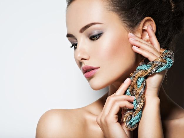 Mooie vrouw met avond make-up sieraden en schoonheid mode foto
