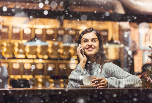 Mooie vrouw met behulp van de telefoon in een café
