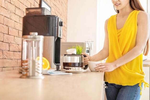 Mooie vrouw met behulp van koffiemachine in de keuken