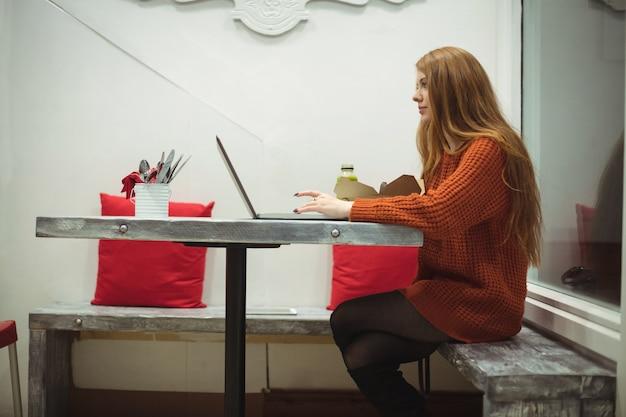 Mooie vrouw met behulp van laptop tijdens het eten van salade