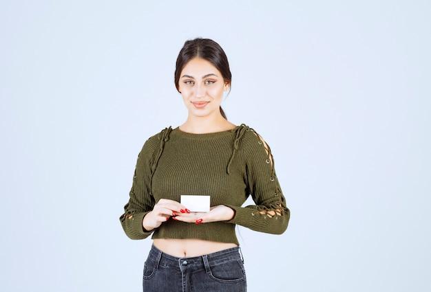 Mooie vrouw met blanco visitekaartje op witte achtergrond.