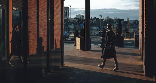 Mooie vrouw met blauw haar die buiten met een computer dichtbij de spiegel loopt