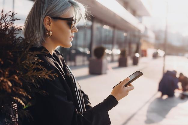 Mooie vrouw met blauw haar poseren tegen de zonsondergang met behulp van een mobiele telefoon en het dragen van een bril