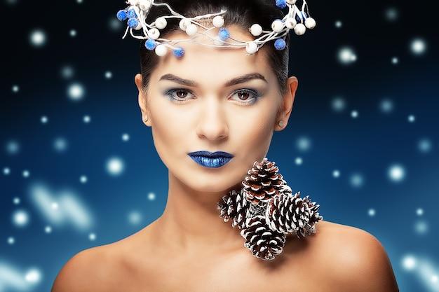 Mooie vrouw met blauwe lippen en dennenappels