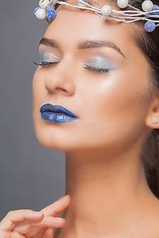 Mooie vrouw met blauwe lippen en kroon