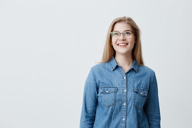 Mooie vrouw met bleke huid en brede, brede glimlach met grote ronde bril, naar boven kijkend, genietend van goed positief nieuws over haar promotie op het werk, poseren tegen een grijze lege achtergrond