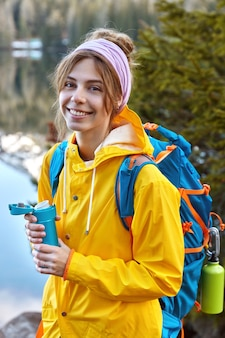 Mooie vrouw met blije gezichtsuitdrukking, gekleed in gele regenjas, draagt rugzak