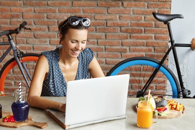 Mooie vrouw met blije glimlach die zonnebril op haar hoofd draagt die internet op laptop doorbladert, newsfeed op sociale media controleert terwijl het gebruiken van vrije wi-fi
