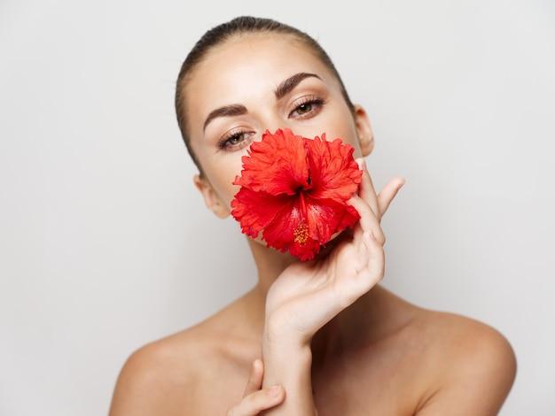 Mooie vrouw met bloem in mond decoratie heldere huid