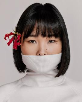Mooie vrouw met bloem over oor