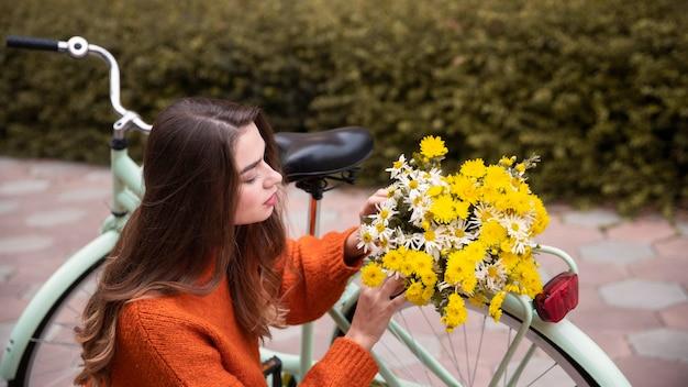 Mooie vrouw met bloemen en fiets buitenshuis