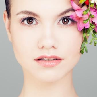 Mooie vrouw met bloemen. gezicht close-up
