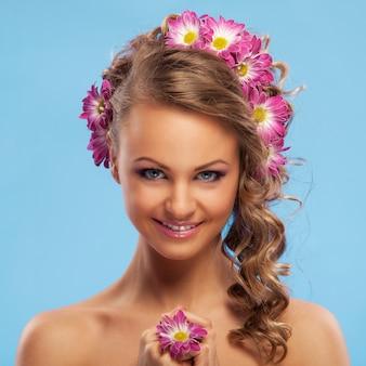 Mooie vrouw met bloemen in haar haar