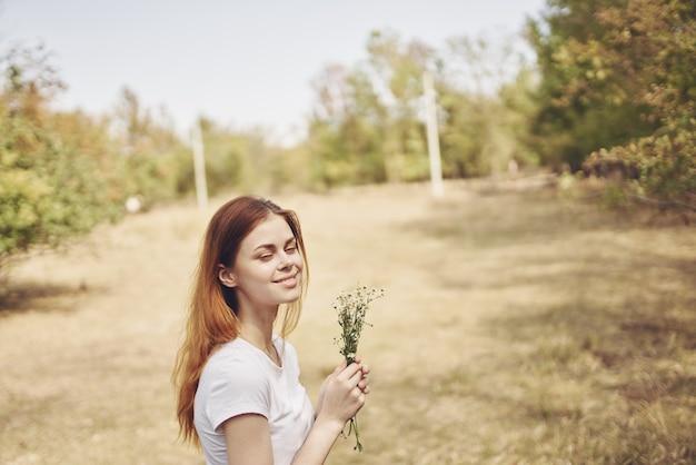 Mooie vrouw met bloemen zon vrijheid reis