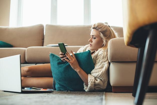 Mooie vrouw met blond haar chatten op mobiel zittend op de vloer en huiswerk