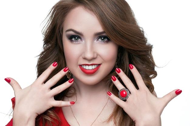 Mooie vrouw met blond haar. mannequin met rode lippenstift en rode nagels. portret van glamourmeisje met lichte make-up. schoonheid vrouwelijk gezicht. perfecte huid en make-up. rode lippen en nagellak