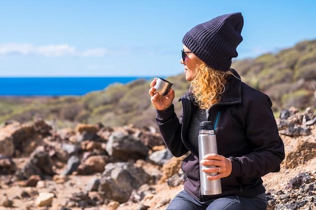 Mooie vrouw met blond krullend haar en zwarte warme muts die geniet van de buitenactiviteit, wat thee of koffie drinkt en naar de zee kijkt