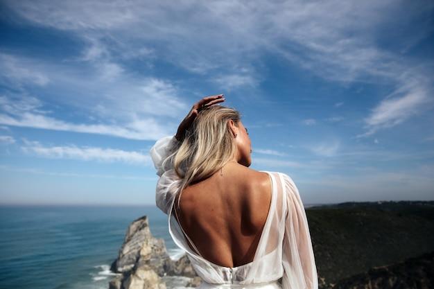 Mooie vrouw met blote rug staat op het panoramische uitzicht op de kust