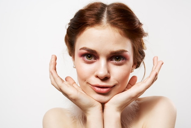 Mooie vrouw met blote schouders lichte make-up pluizige oorbellen cosmetica glamour