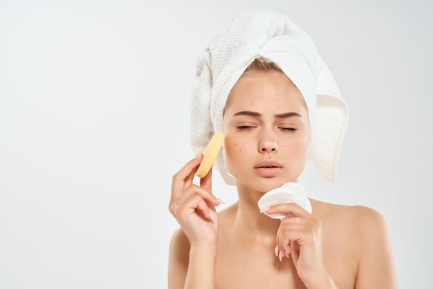 Mooie vrouw met blote schouders spons schone huid gezondheid lichte achtergrond
