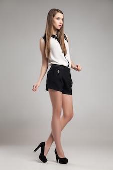 Mooie vrouw met blouse en korte broek poseren in studio