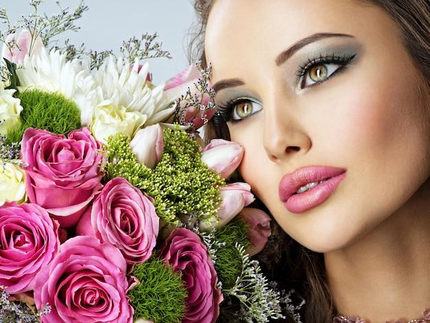 Mooie vrouw met boeket verse spting bloemen op gezicht. mooi meisje met maniermake-up