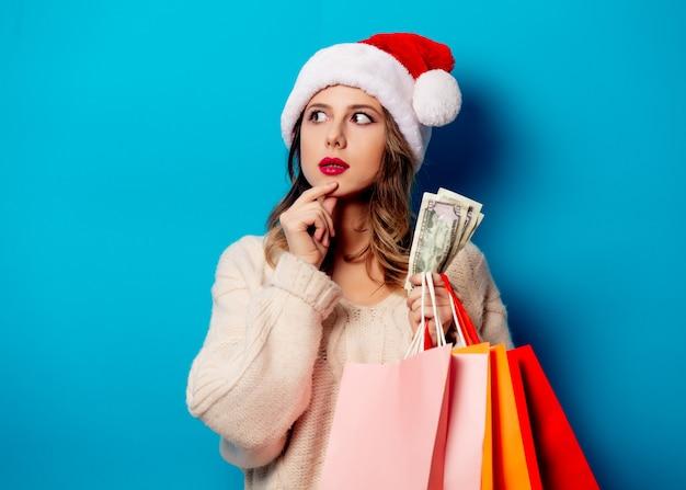 Mooie vrouw met boodschappentassen en geldklok op blauwe muur