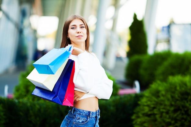 Mooie vrouw met boodschappentassen in de buurt van winkelcentrum