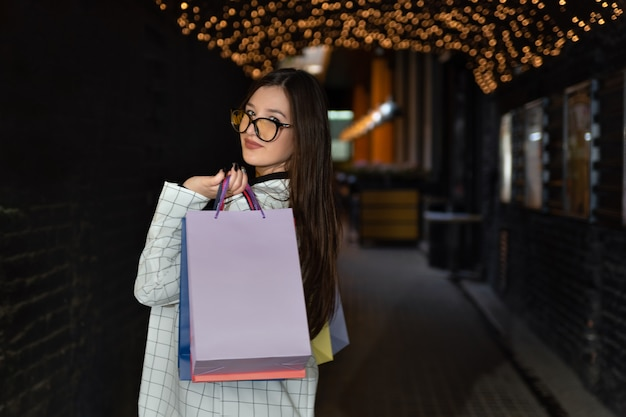 Mooie vrouw met boodschappentassen kijkt over haar schouder. succesvol winkelen.