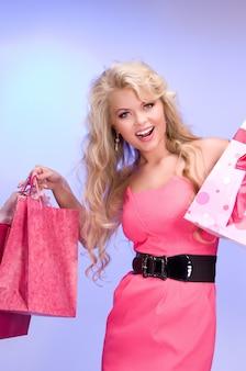Mooie vrouw met boodschappentassen over blauw
