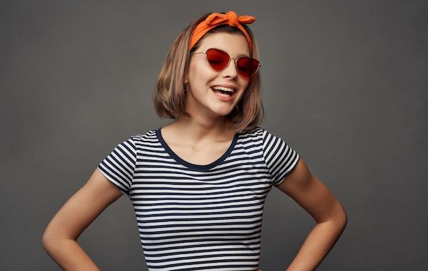 Mooie vrouw met bril in een gestreepte t-shirthoofdband