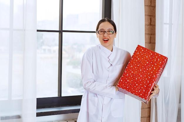 Mooie vrouw met bril in laboratoriumjas met grote huidige doos in de buurt van raam.