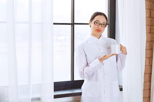 Mooie vrouw met bril in laboratoriumjas poseren met kopje koffie in de buurt van raam.
